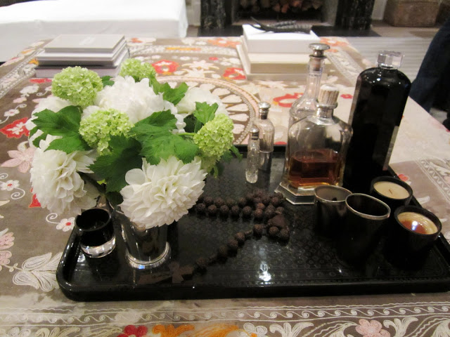 A large dark tray turns an ottoman into a coffee table vignette with green and white flowers, scented oils, a rosary, and candles