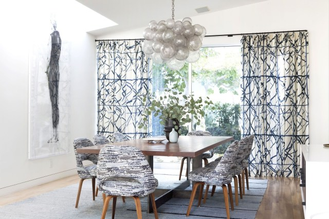 Dining room with bubble chadelier and graphic printed curtains and chairs