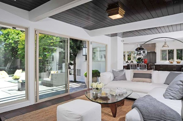 Den has wood paneled ceiling and a dark wood floor with a sea grass area rug and a glass coffee table. A white sectional sofa has black and white accent pillows with a metal arched lamp. The room has a view of the backyard and pool thanks to the large window and sliding glass door