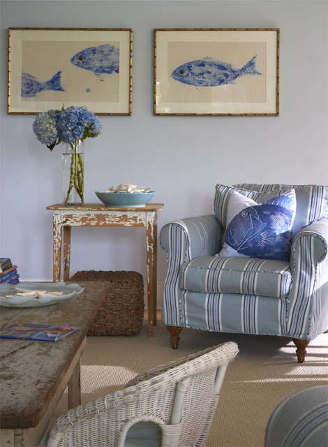 Living room with blue and white white striped armchair, reclaimed wood side table, white wicker chair and blue walls with framed pictures of blue fish