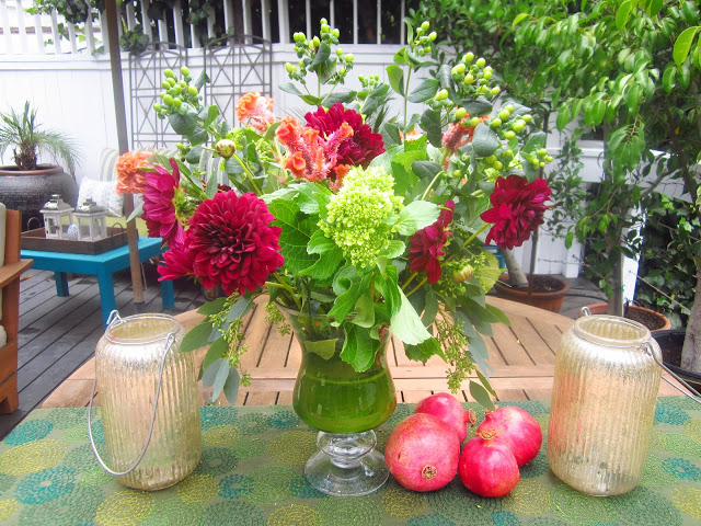 completed flower arrangement with 4 pomegranates on a wooden patio table