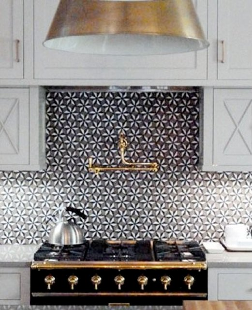 Kitchen with white cabinet and drawers, black appliances with brass accents and a pinwheel tile backsplash