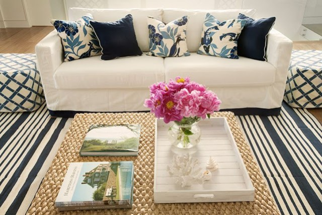 living room with blue and white striped rug, white couch with navy and bird printed accent pillows, two ottomans with blue trellis acting like side tables, and a woven ottoman coffee table