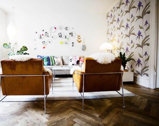 living room walls wallpaper flower floral purple green white leather chairs sofa plates herringbone wood floor decorate home