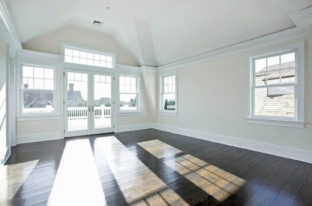 empty bedroom with wood floors and large windows