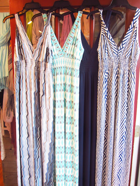 Four summer maxi dresses hanging from black hangers