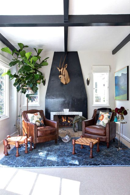 Den with leather armchairs, black fireplace and an antelope head