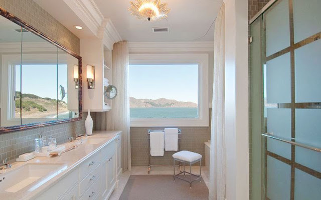 Master bathroom with grey subway tiles, a white counter and drawers, white floor length curtains, a towel rack and an ocean view