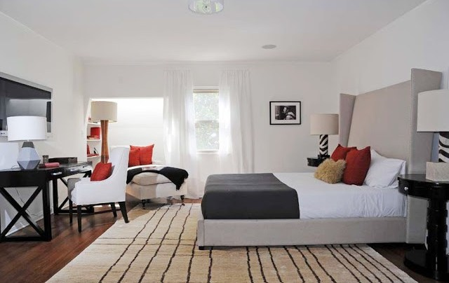 Guest bedroom with taupe wing back headboard, a black writing desk with a white armchair with red and brown accent pillows, wood floor with a striped area rug, black oval nightstands and a beige chaise longue with orange accent pillows near the window