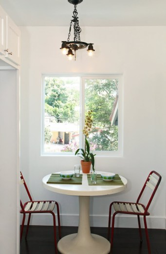 Breakfast nook in a Spanish Style home with two red chairs, a round white table and Koa wood floor