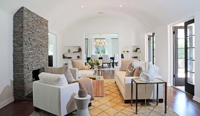 Living room with arched ceiling, a stone fireplace, black French doors, wood floors, a Moroccan style rug with a white sofa and two matching armchairs with neutral accent pillows