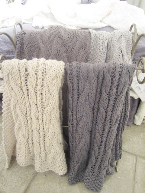 Close up of Pom Pom's chunky knit throws in light purple, grey, white and cream.
