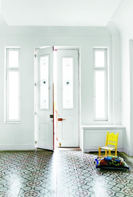 white entry way with tiles and a child's chair
