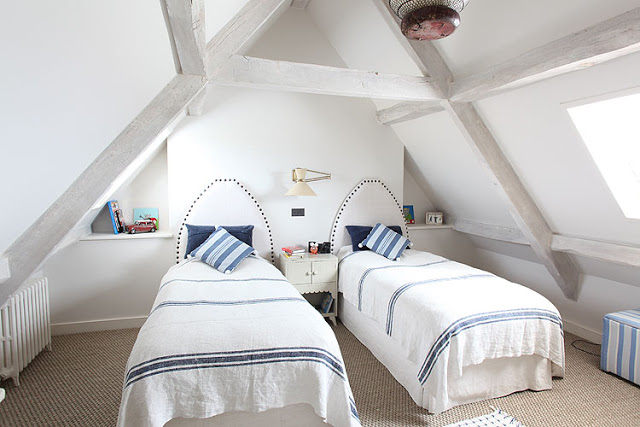 bedroom with two twin beds with white headboards and blue and white striped bedding with matching accent pillows