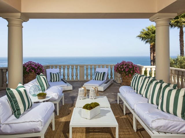 Outdoor patio with green and white stripe pillows, white outdoor chairs and an ocean view