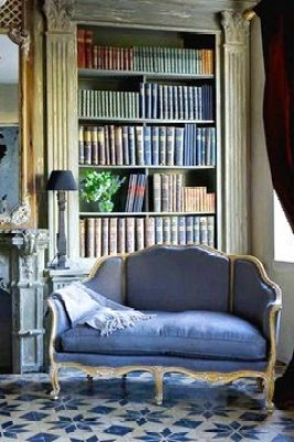 Library in a mansion in Belgium with carved oak book shelves, tile floor, blue settee and a large fireplace with with a modeled mantel and traditional mirror