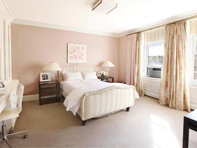 Bedroom with striped upholstered head and footboard, two wooden night stands, pale pink walls, carpeted floor and floor length, floral print curtains