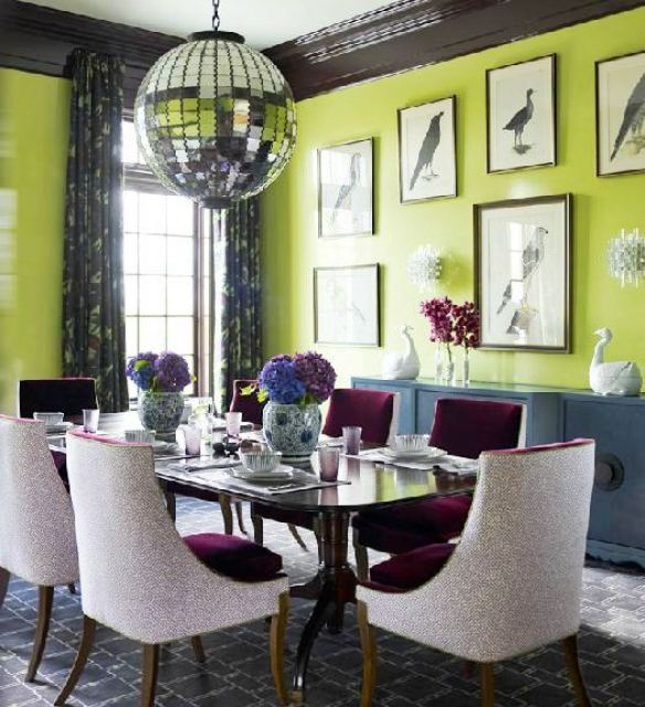 Alternative view of the dining room with apple green walls with framed prints of birds, purple chairs, a graphic grey and white rug, a disco ball pendant light, an encasement window with floor length patterned curtains and a blue-grey wall console