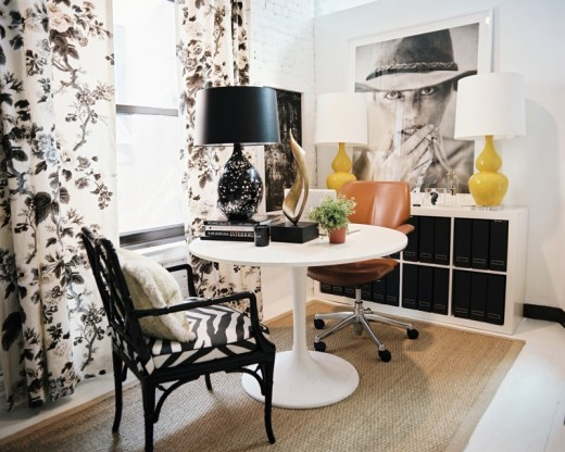 City office with white painted brick walls, Schumacher's Pyne Hollyhock chintz curtains,  Saarinen tulip table, a black painted faux bamboo chair and a yellow table lamp