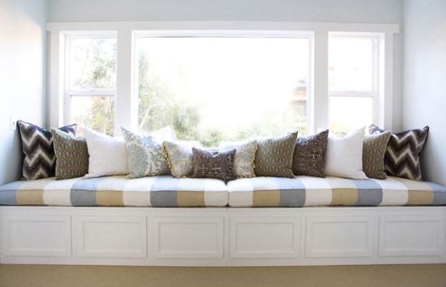 long window seat with striped olive green, blue and white cushions and patterned accent pillows