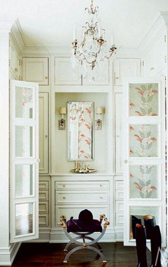 White dressing area with wood floor, crystal chandelier and mirrored doors reflecting floral curtains