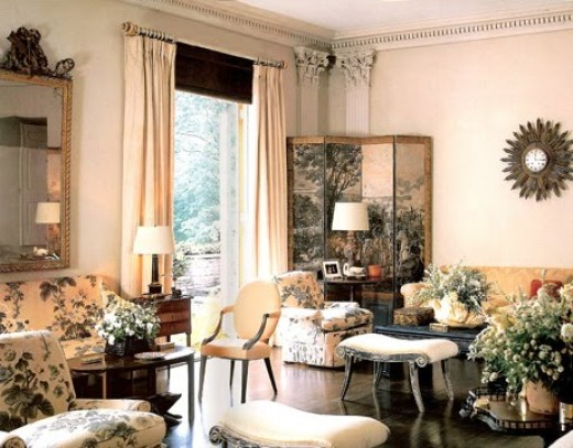 Vintage 1960s living room with chintz sofas and armchairs. The room has a dark wood floor, moulded crown detailing and a large window with floor length cream colored curtains