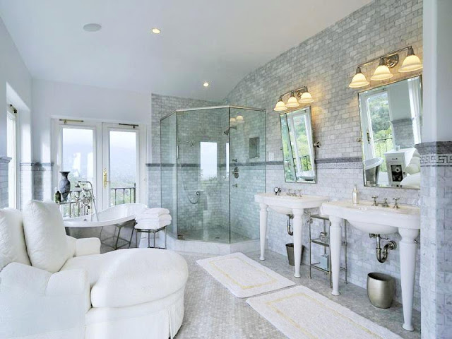 Master bathroom with cararra marble walls, penny round mosaic tile floor, two pedestal sinks, a stand alone tub and large windows