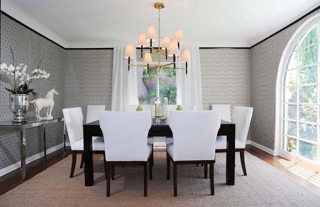 Dining room with graphic wallpaper, black crown molding, a black table surrounded by white chairs, a brass chandelier, and an arched picture window