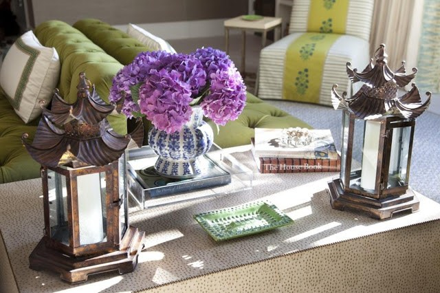 vignette in a living room featuring a textured coffee table with nail head trim, Chinoiserie accents in the form of lanterns and blue and white urn holding purple hydrangeas and a Lucite tra