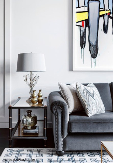 Grey living room in a Sydney loft with dark wood floor, geometric rug, grey sofa with nail head trim and a faux bamboo side table