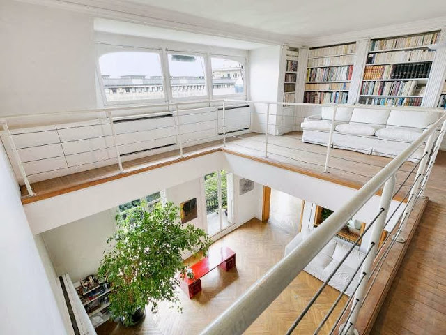 Second floor of a Paris apartment with built in bookshelves and a white sofa
