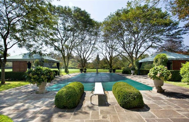 Mansion's backyard with an outdoor pool and diving board