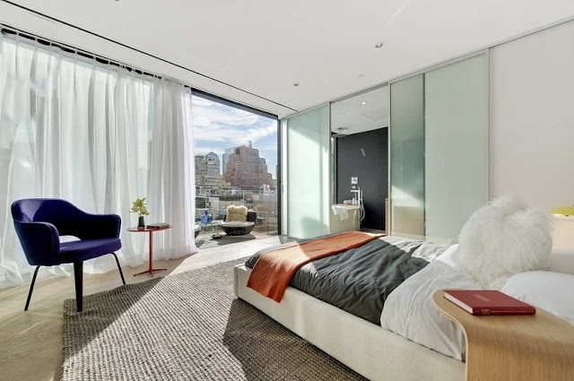 modern master bedroom with glass wall, sliding door, wood floor and orange and purple accents