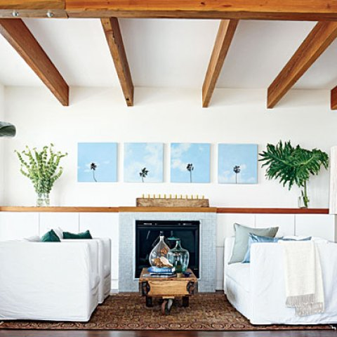Living room with white walls and exposed ceiling beams, wood floor, white armchairs and sofa with blue accent pillows, a fireplace with blue tile surround and on the wall above the fireplace are four paintings of the tops of palm tress bookended by a glass vase of palm leaves