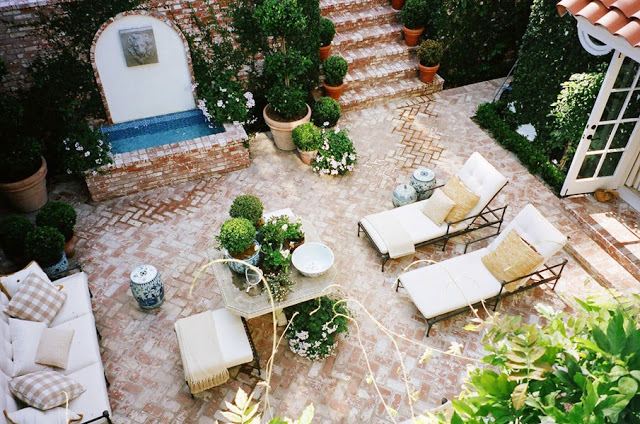 ariel view of a brick lined outdoor patio with metal lawn chairs with neutral cushions, a matching sofa, a small brick fountain and lots of potted plants