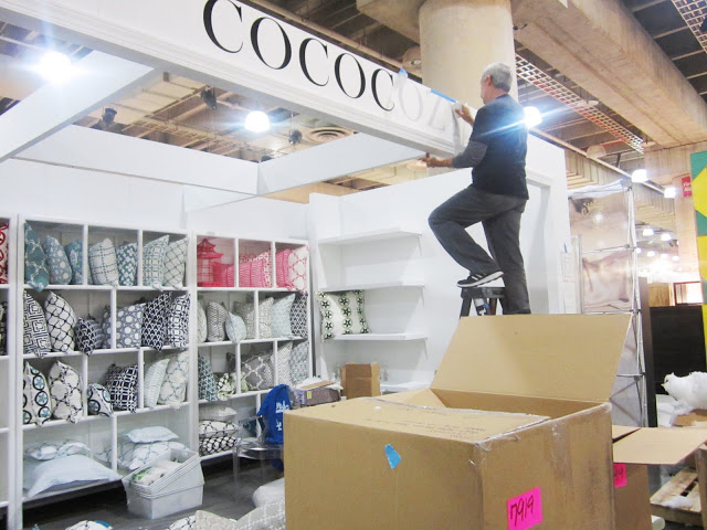 Vinyl lettering going up at the COCOCOZY booth at the New York International Gift Fair
