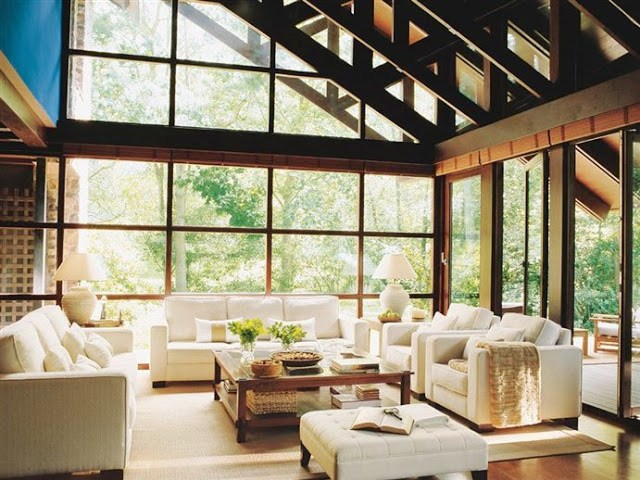 Living room in a converted mill with the walls replaced with glass windows and doors, white sofas and arm chairs and a wood coffee table