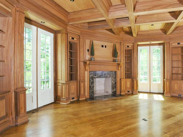 Wood paneled library/home office with french doors, visible beams a fireplace