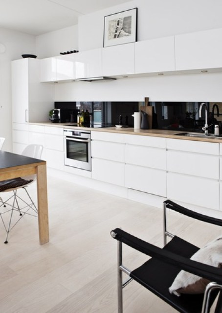 white kitchen black backsplash glossy shiny modern cabinets one wall open floor plan apartment house home decor furnishings interior design