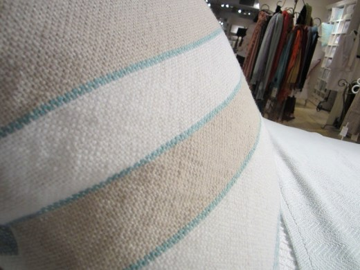 Close up of one of the woven blue, white and beige striped pillows