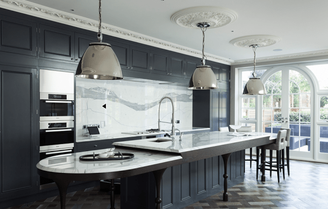 Kitchen in a suburban London home with dark grey cabinets, marble counter tops and backsplash, stainless appliances, silver pendant lights, carved crown moulding, ceiling medallions, parquet wood floors and leather barstools
