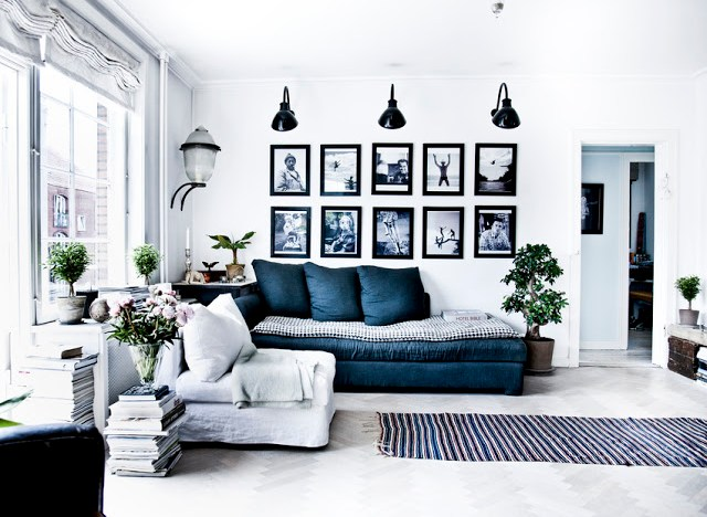 Modern living room light herringbone wood floor black framed pictures white walls black wall sconces squishy daybed and armchair