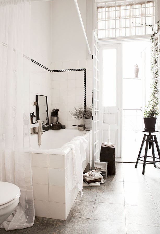 Black and white bath with black accents and french door leading to patio