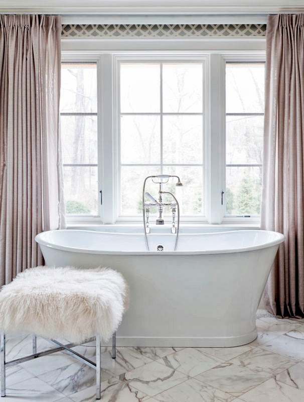 Stand alone bathtub in a girly bathroom with marble floor, floor length curtains and a furry stool