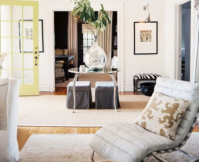 white entry way with a light yellow door, wood floor, a sea grass rug, a round mirror table holding a large tear drop vase with a plant, two grey ottomans are under the table, in the foreground there is modern white chair with a curved back