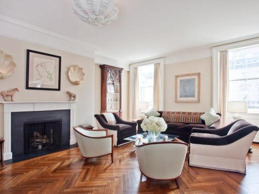 White family room in a park avenue apartment with herringbone wood floor, fireplace, white club chairs, dark purple sofa with matching armchairs and large windows with floor length curtains