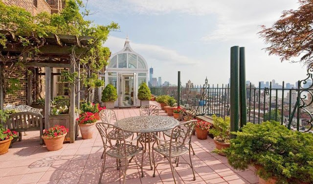 terrace with a gazebo, rows of potted plants, a metal table with matching chairs and an amazing view of New York City