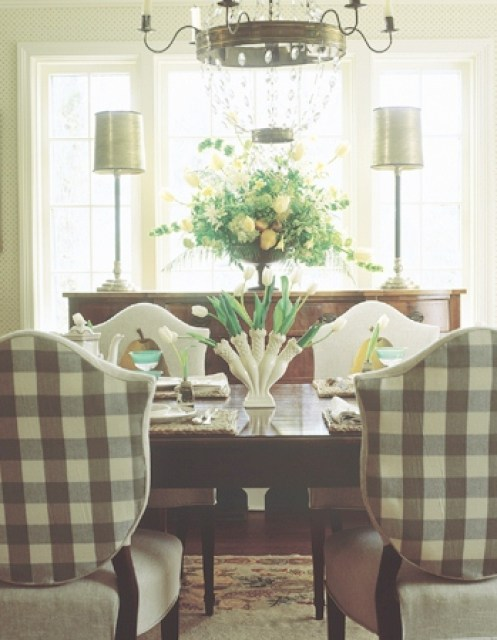 Dining room with gingham upholstered Louis XIV chairs, a wood table, floral arrangement and crystal and brass chandelier
