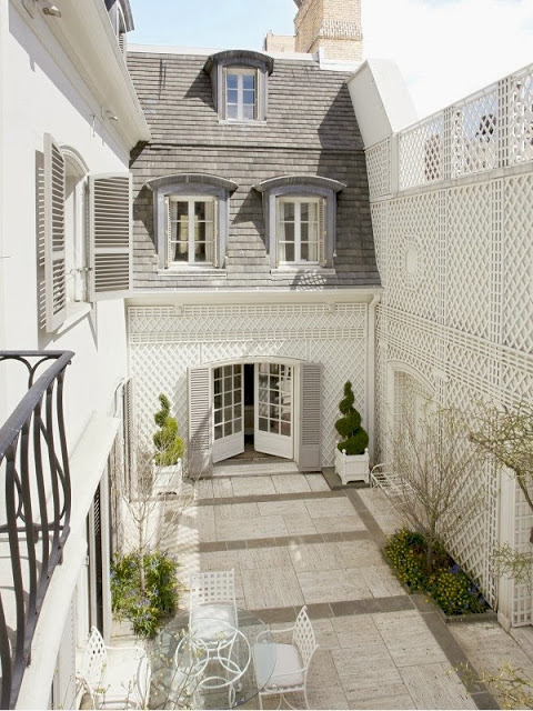 Outdoor patio with enclosed courtyard with a white trellis wall