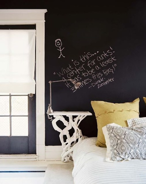 Bedroom with French doors with Roman shades, a white nightstand designed in the shape of branches holds a silver clamp light and instead of a headboard, the white bed with green and paisley accent pillows, has a black chalkboard